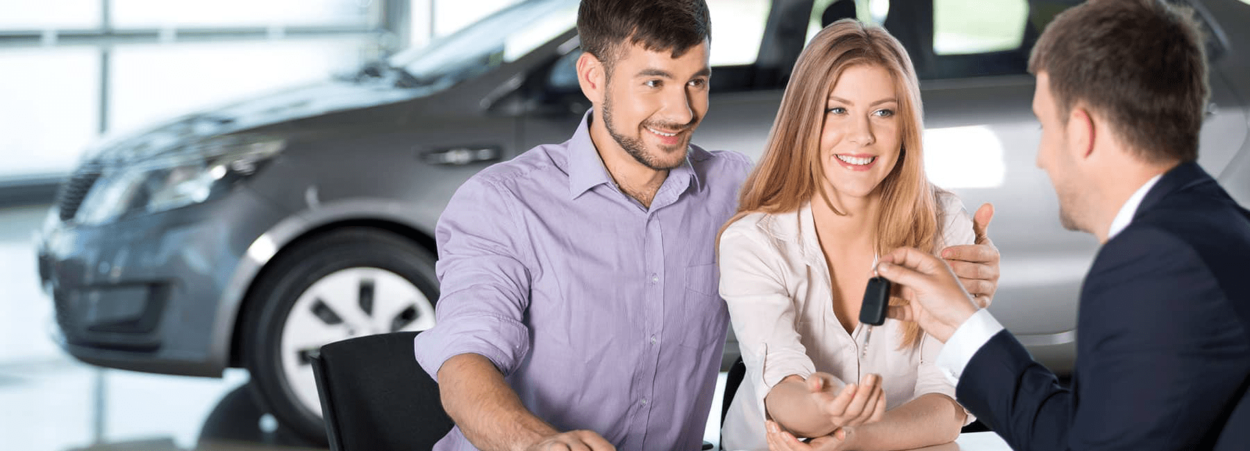 smiling couple meets with finance officer in car showroom