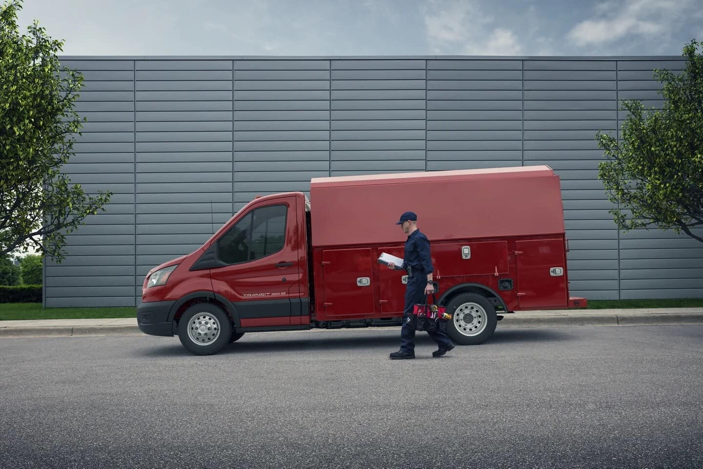 electrician walks past his red Ford Transit truck