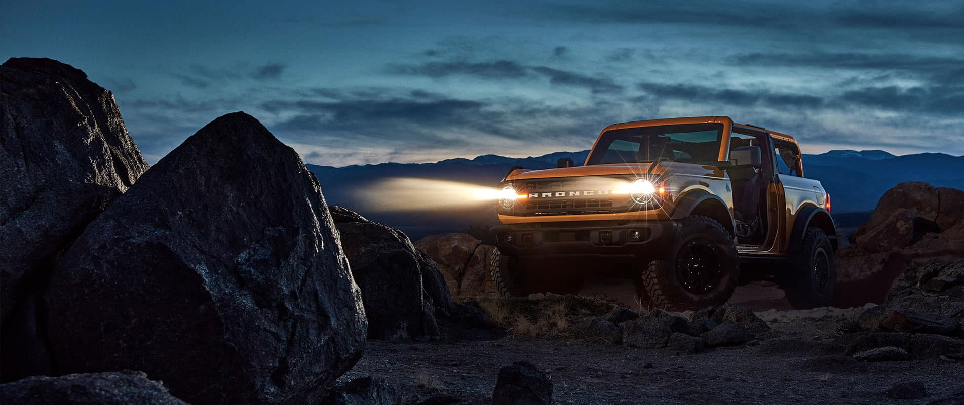 Bronco parked at night on rocky terrain