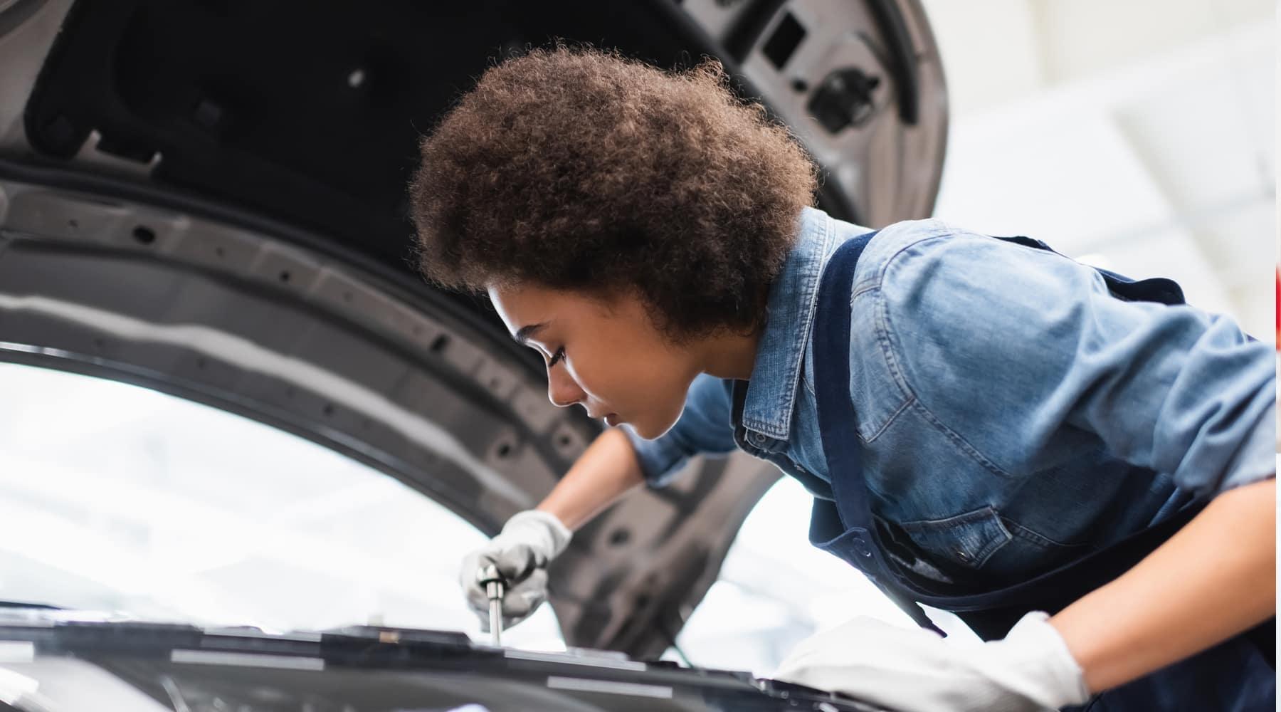 female technician repairing car engine