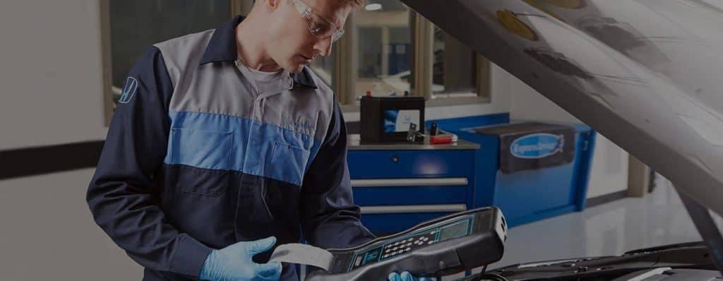 Honda Service Technician checks engine with engine sensor