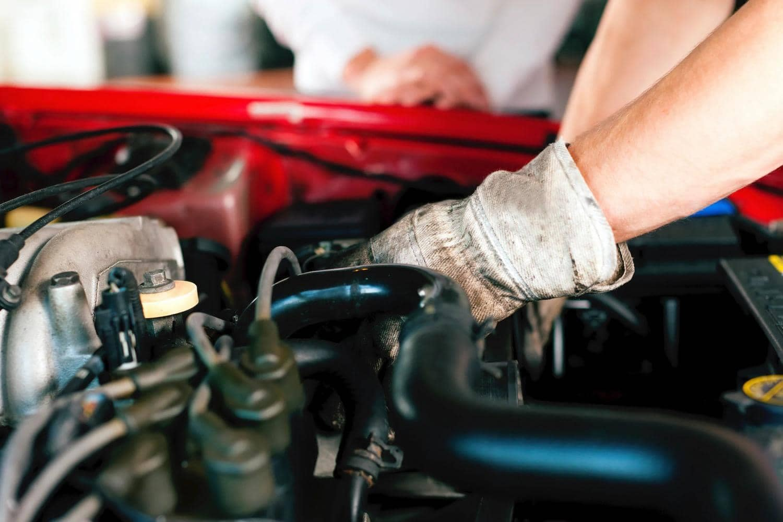 Technician fixes car engine