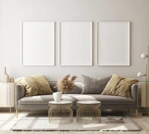 Three White Picture Frames Hanging above Gray Couch with Beige Pillows