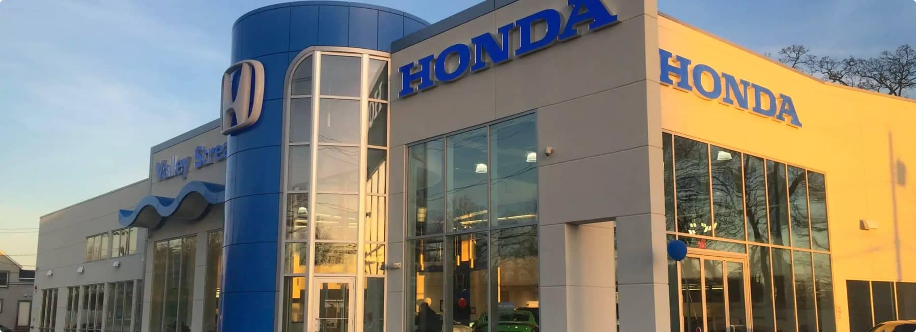 An exterior shot of a Honda dealership during the day