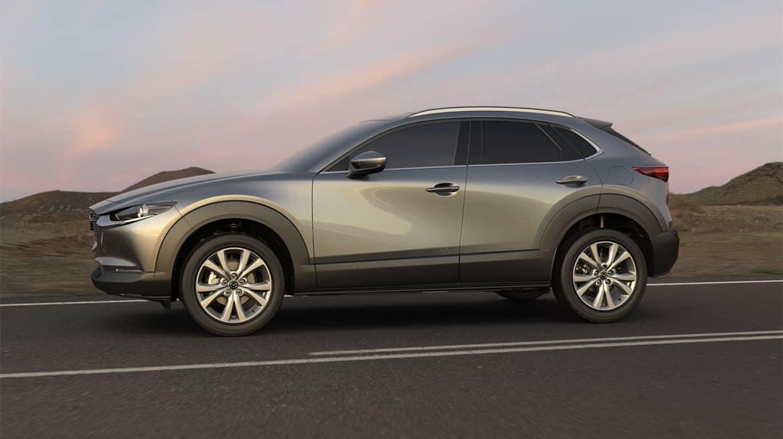 Mazda CX-30 drives along desert highway as sun sets