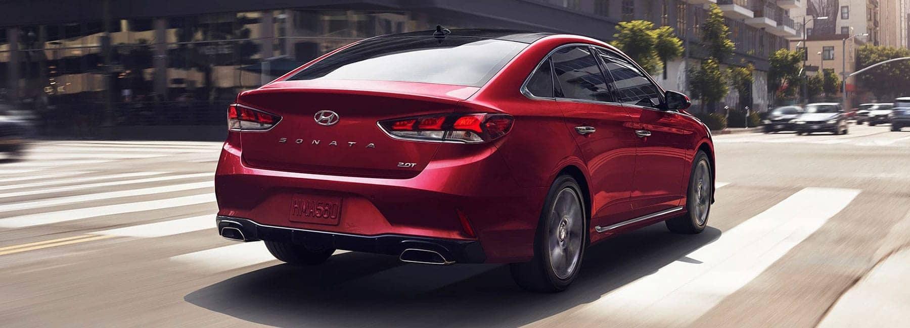 Red 2019 Hyundai Sonata driving down a city street