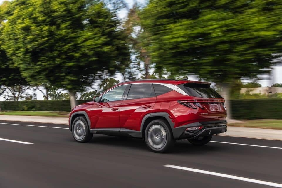 2022 Red Tucson side view driving on open road