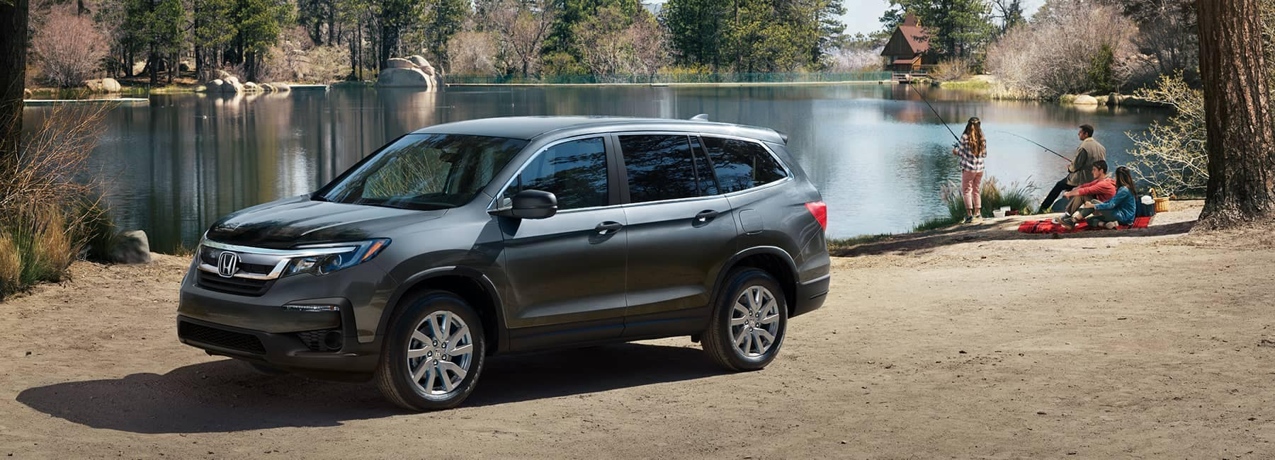 2021 Dark Grey Honda Pilot parked next to a forrest lake