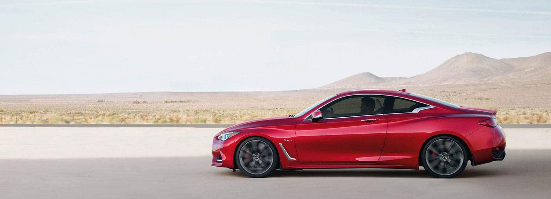 The sideview of a red 2019 INFINITI Q60 driving down a road in a desert