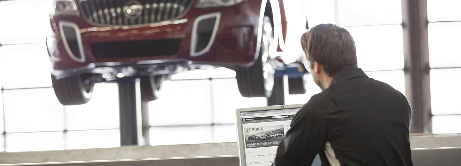 Buick service technician looking at car raised up