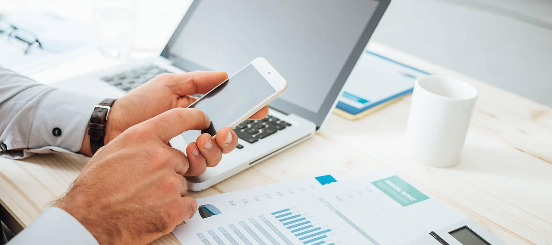 Person using smartphone with laptop and finance papers on desk