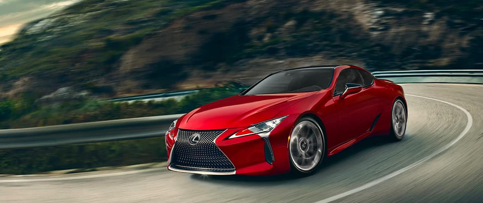 red lexus driving fast along mountain side