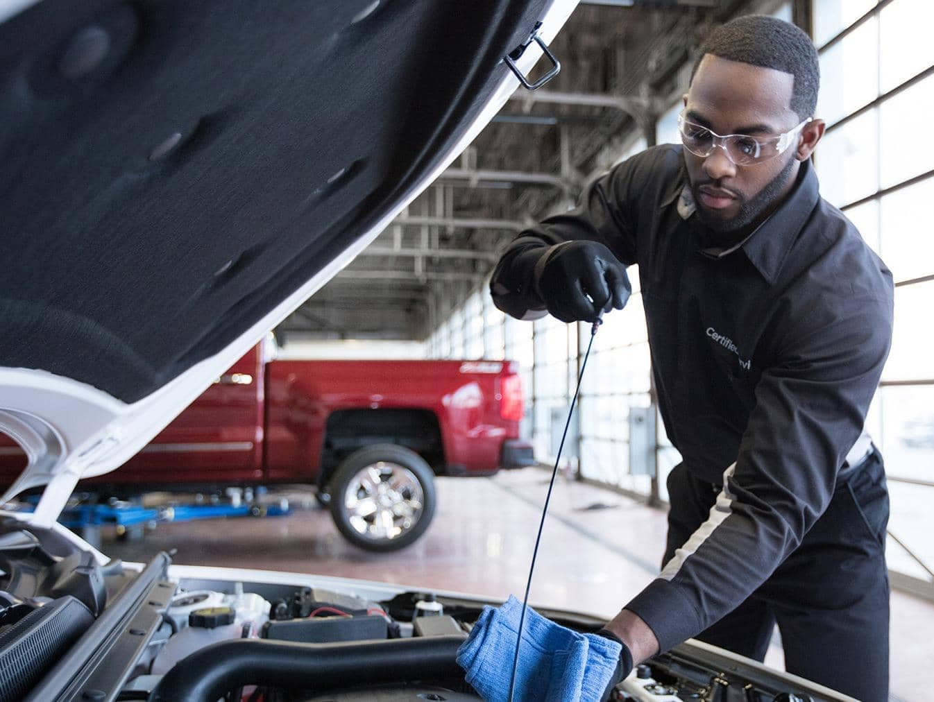 Chevrolet Service Technician inspecting oil