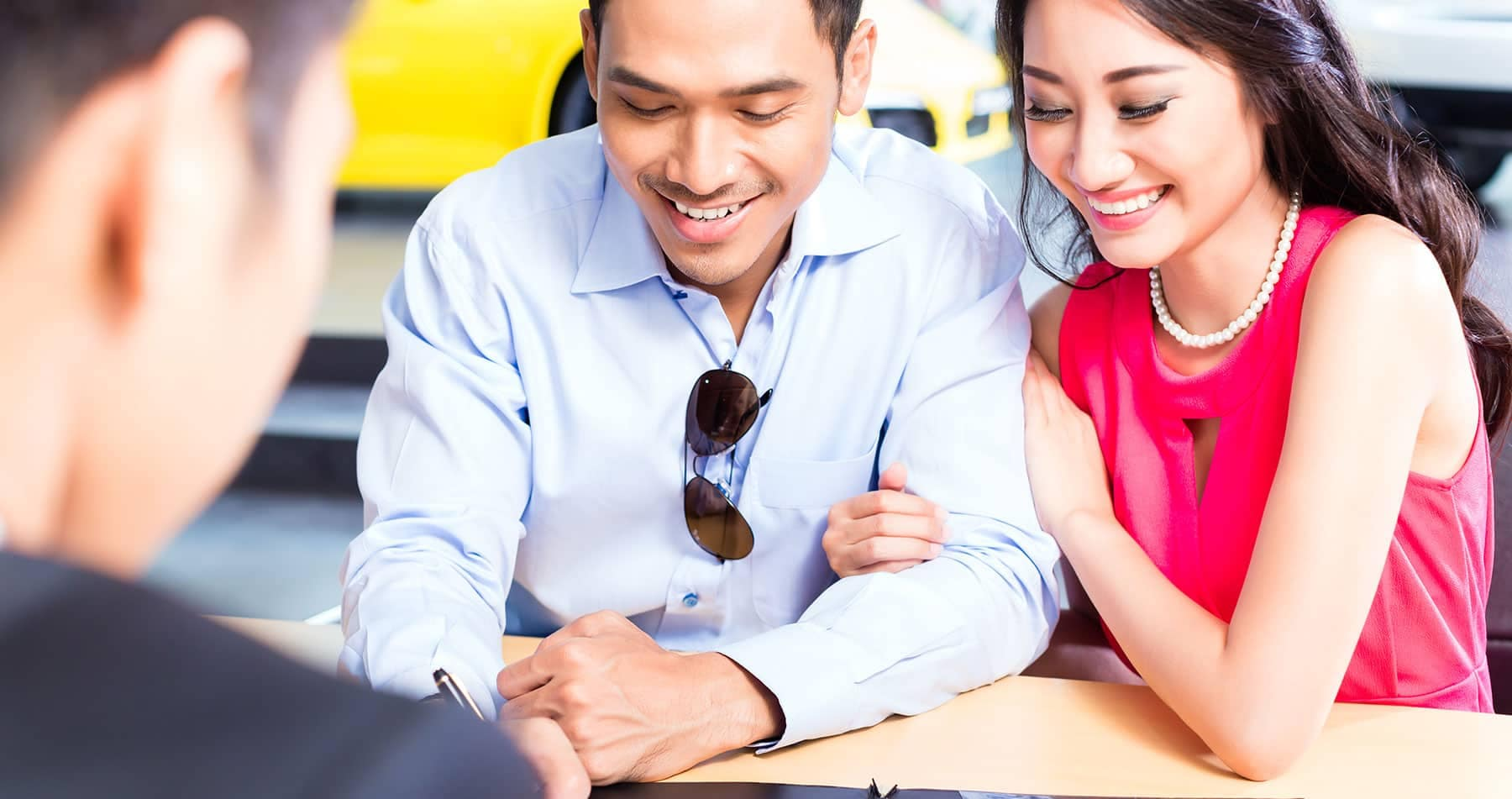 a smiling couple is at finance desk at dealership