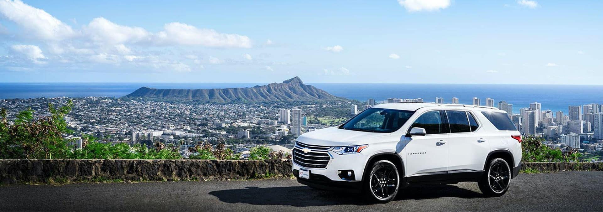 White Chevrolet SUV sitting on the top of a hill with a view