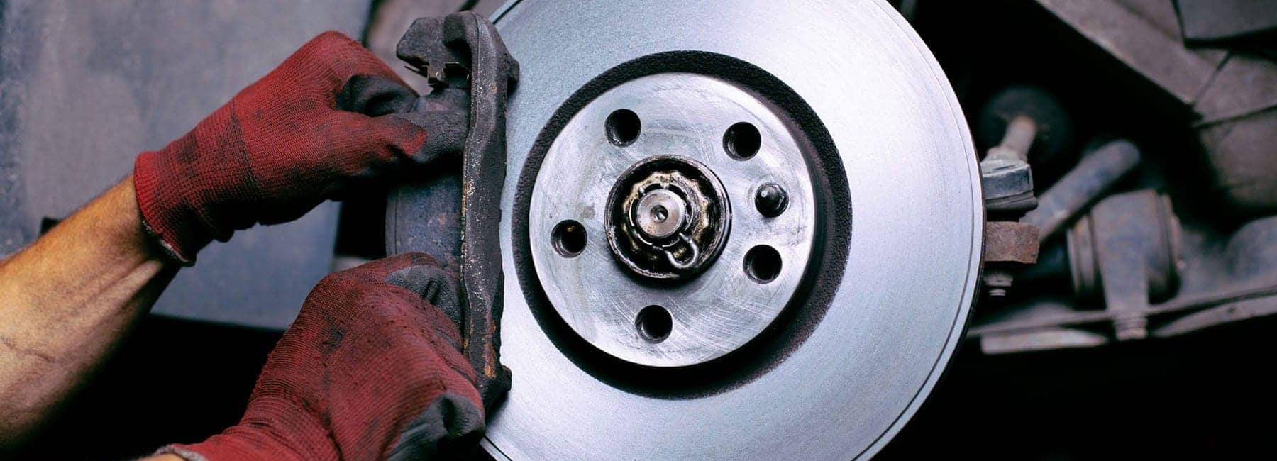 Closeup of a mechanic replacing a brake pad on a car