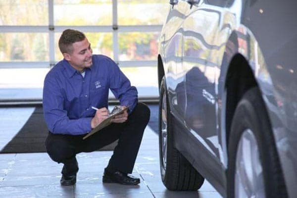 Service representative taking a look at a car