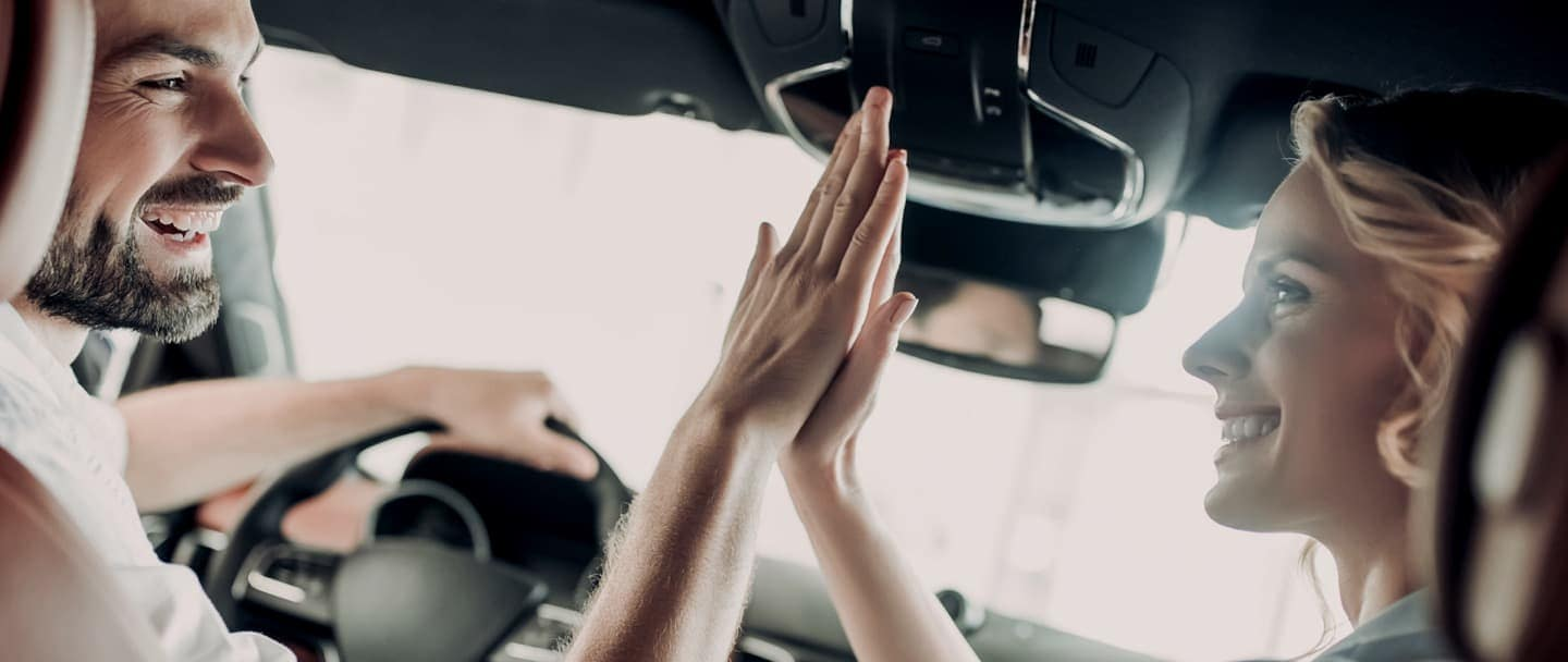 Two people touching hands in car smiling