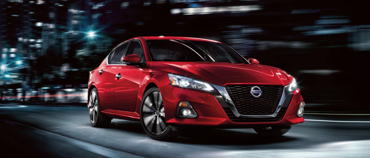 A red 2019 Nissan Altima S driving down the city street at night