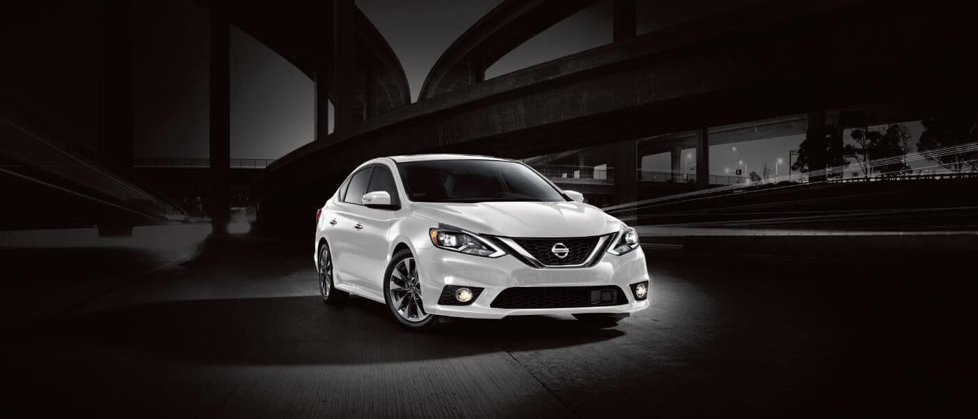 A white 2019 Nissan Sentra parked under highways at night