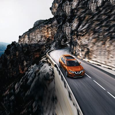 An orange 2019 Nissan Rogue driving through a winding mountain road