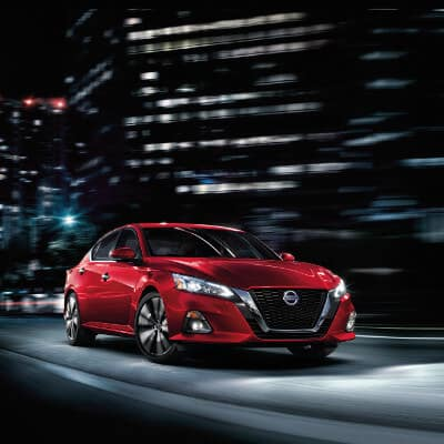 A red 2019 Nissan Altima driving down a city street