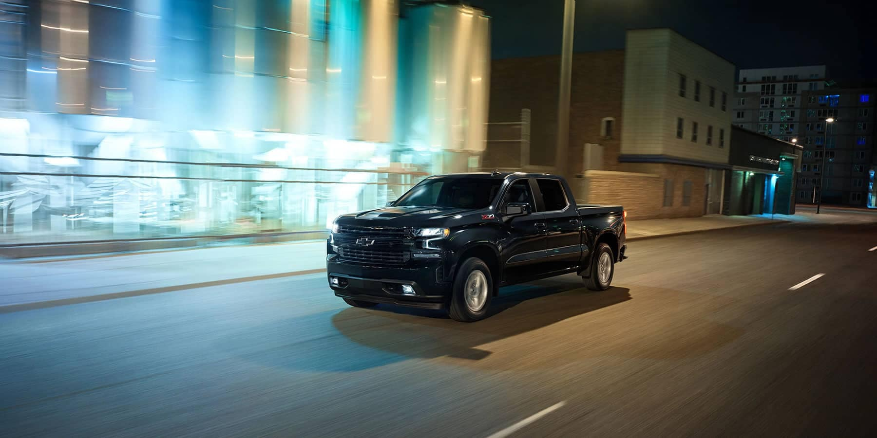 Chevrolet Silverado driving on the city street at night