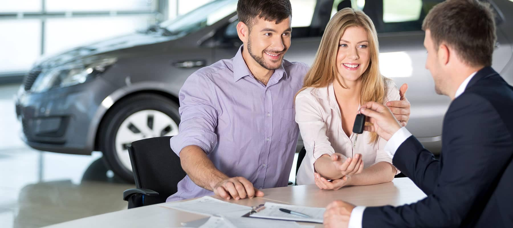 young smiling couple accepting car keys from dealer
