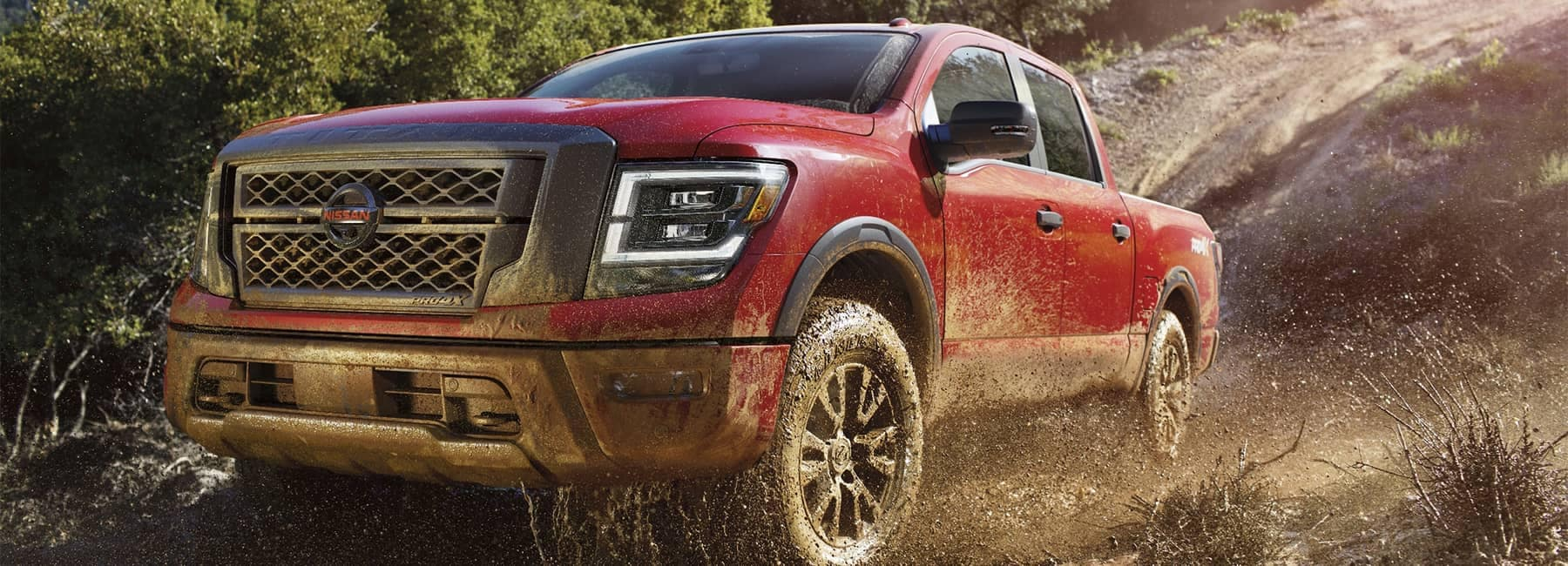 A 2021 Red Nissan Titan truck off roading in dirt