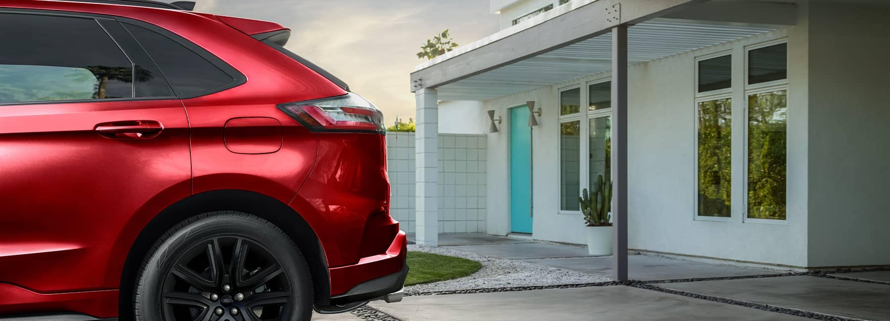 Red 2021 Ford Edge parked in front of a modern home
