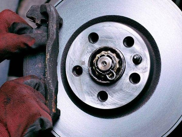 Close up of a mechanic replacing a brake pad on a car