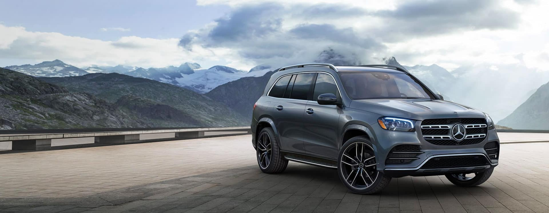 Grey Mercedes Benz SUV on a brick surface with mountains in the background