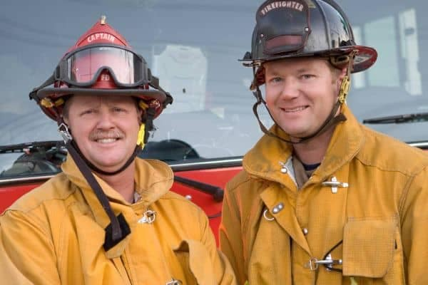Two firemen standing in front of a firetruck