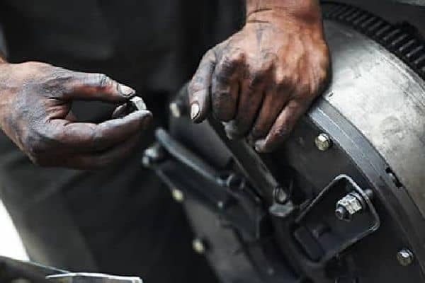 Hands fixing a cars breaks