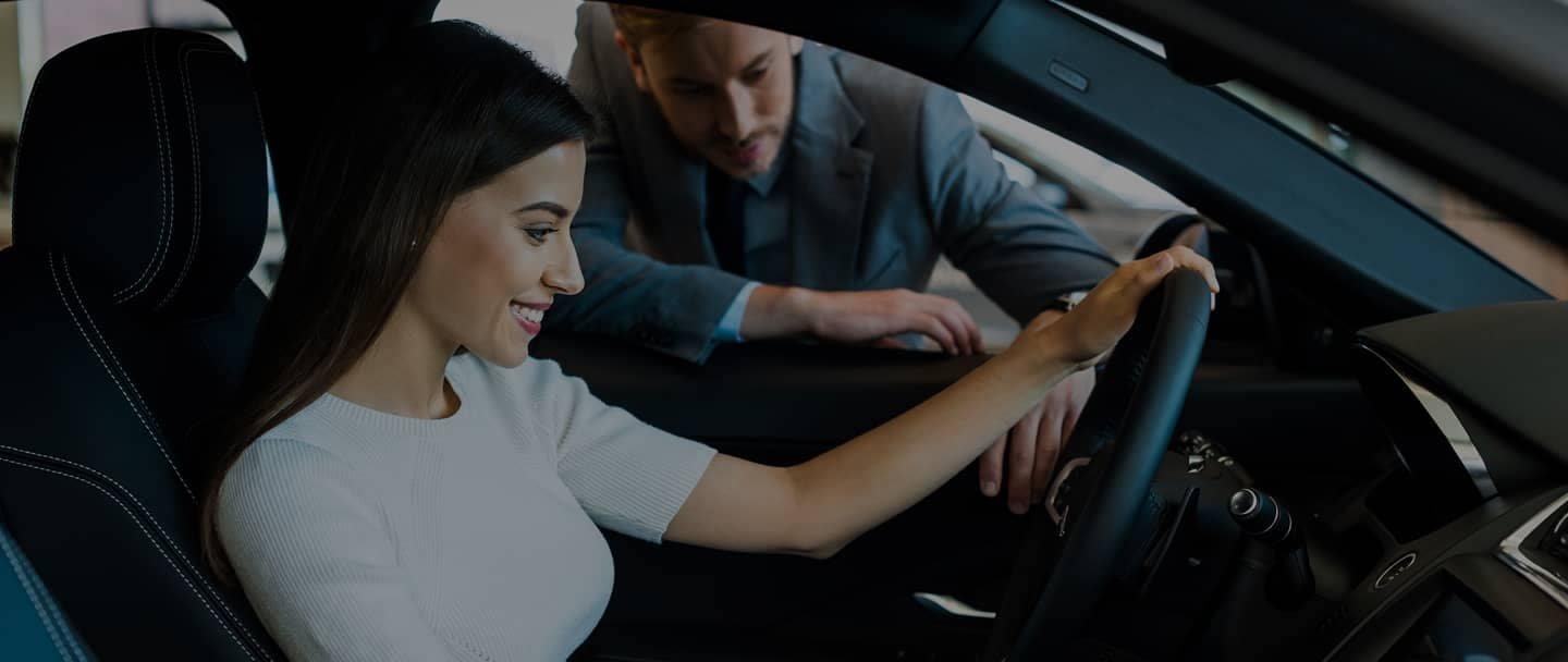Woman in drivers seat talking to man outside of car
