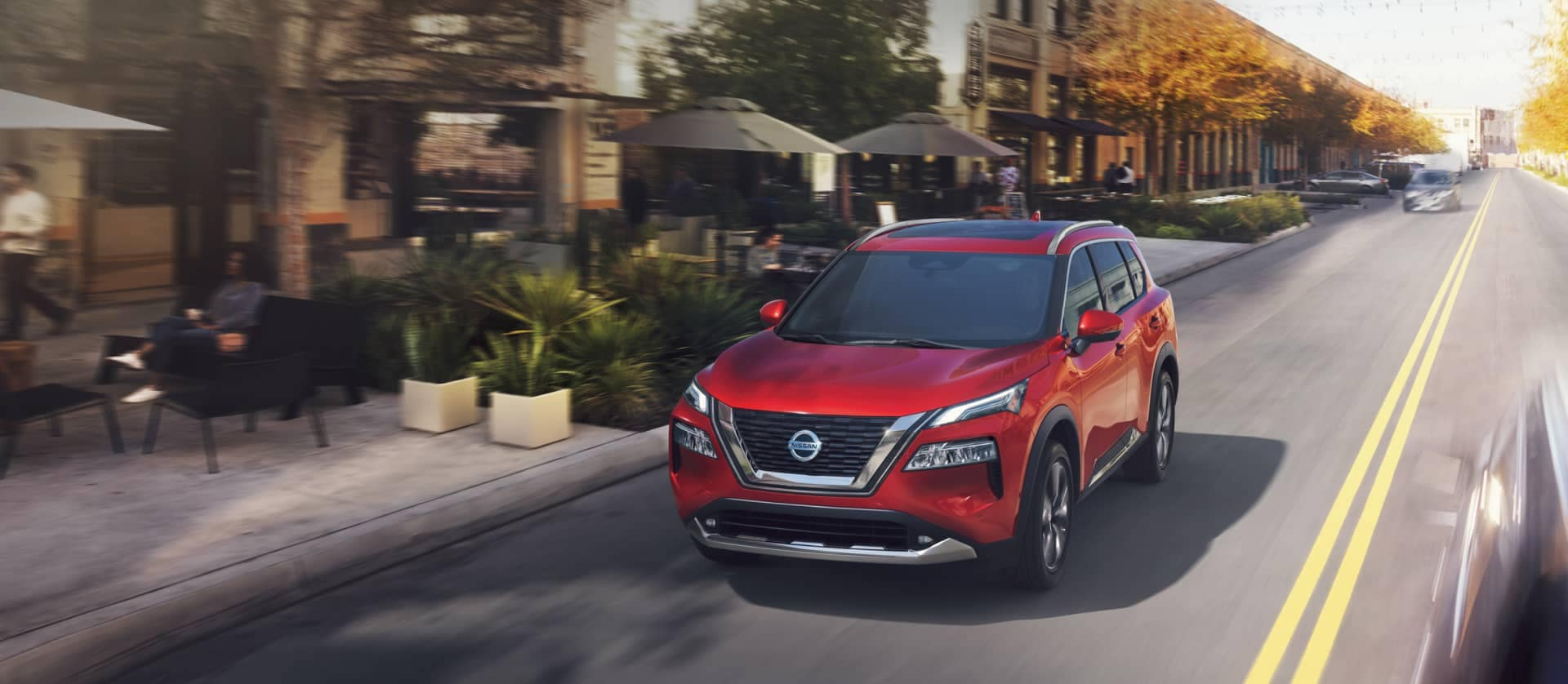 new red nissan rogue driving down city street