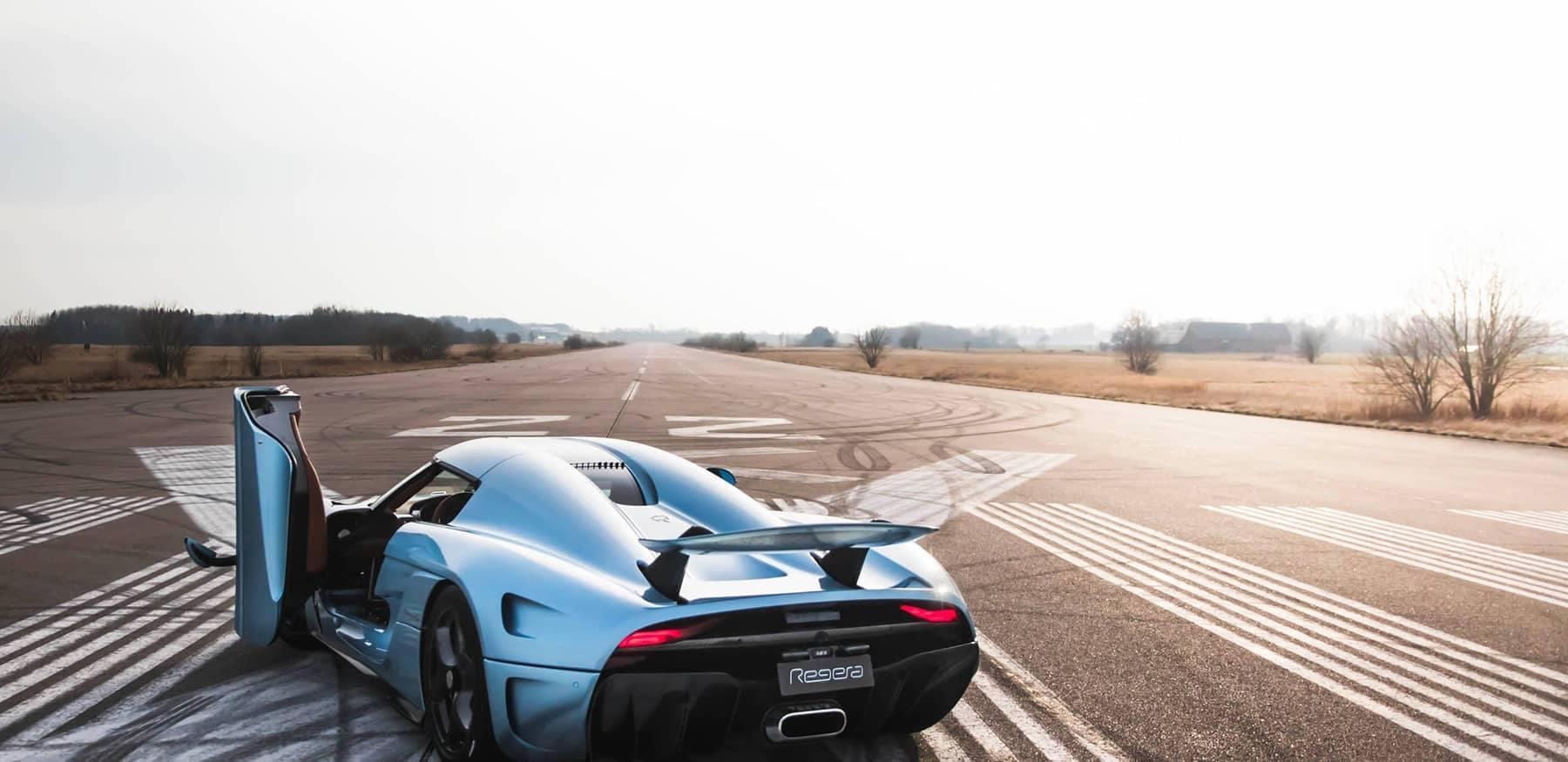 Regera with passenger door open on open road