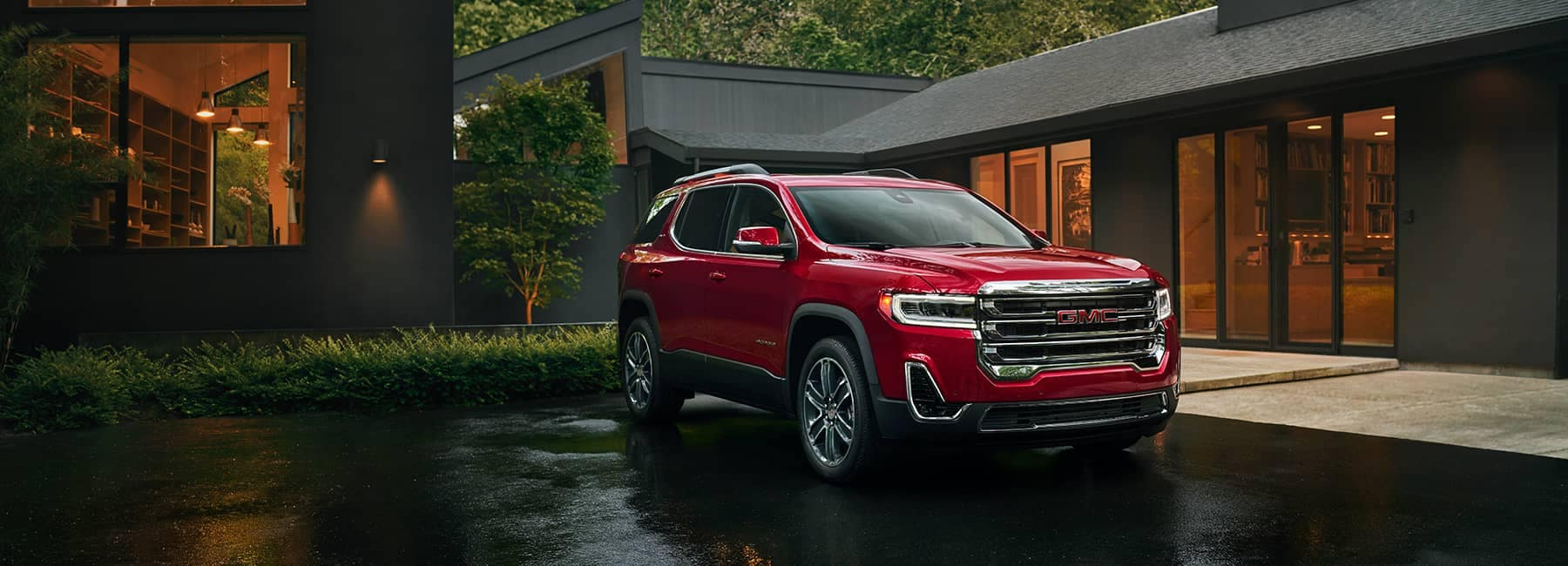 Red 2020 GMC Acadia parked in front of home