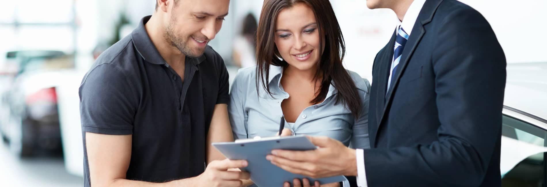 Man and Woman Looking at Documents with Dealer