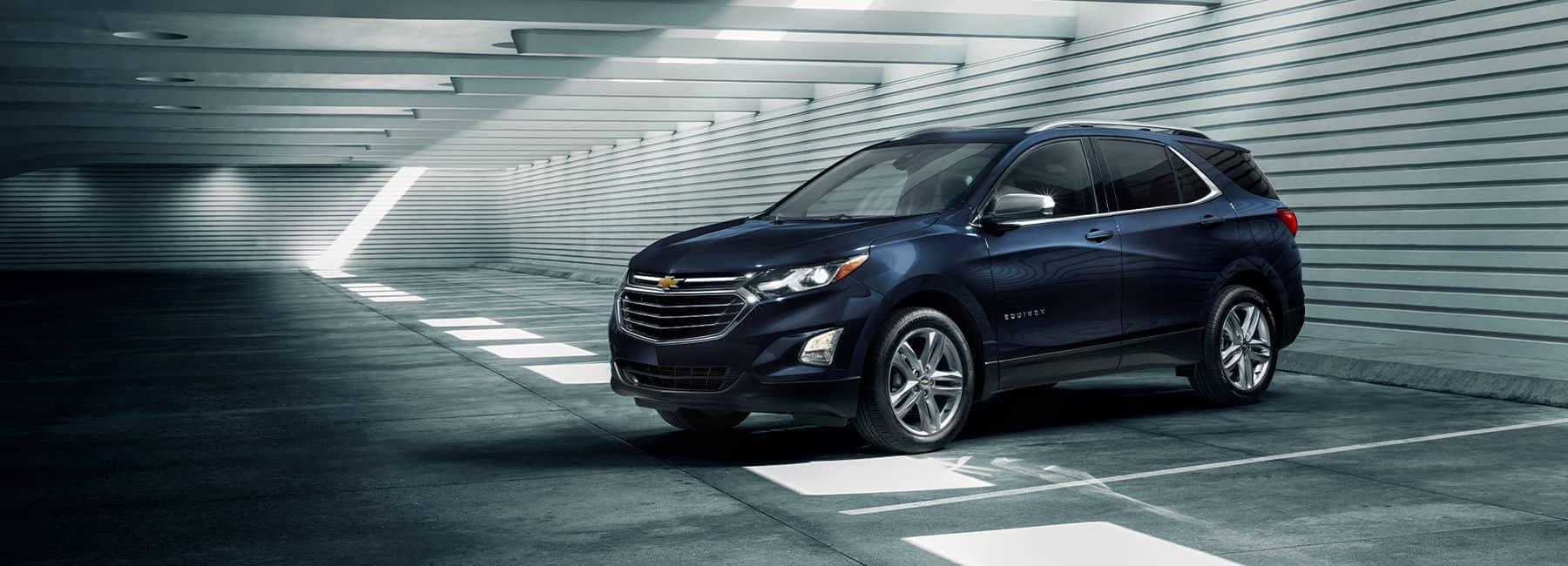 A blue 2021 Chevrolet Equinox parked inside a parking garage