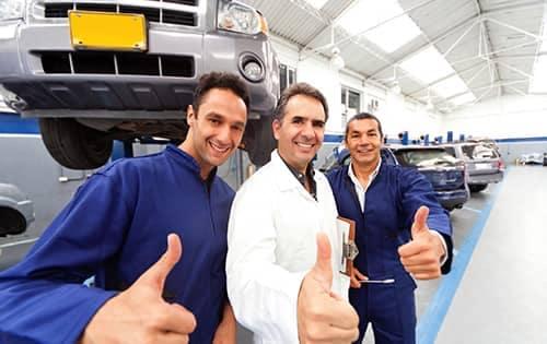 Three mechanics giving the thumbs up