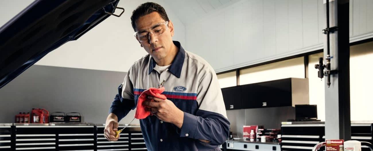 Ford mechanic checking oil