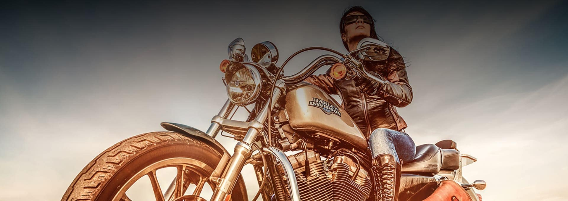 Woman on a harley davidson facing the sunset