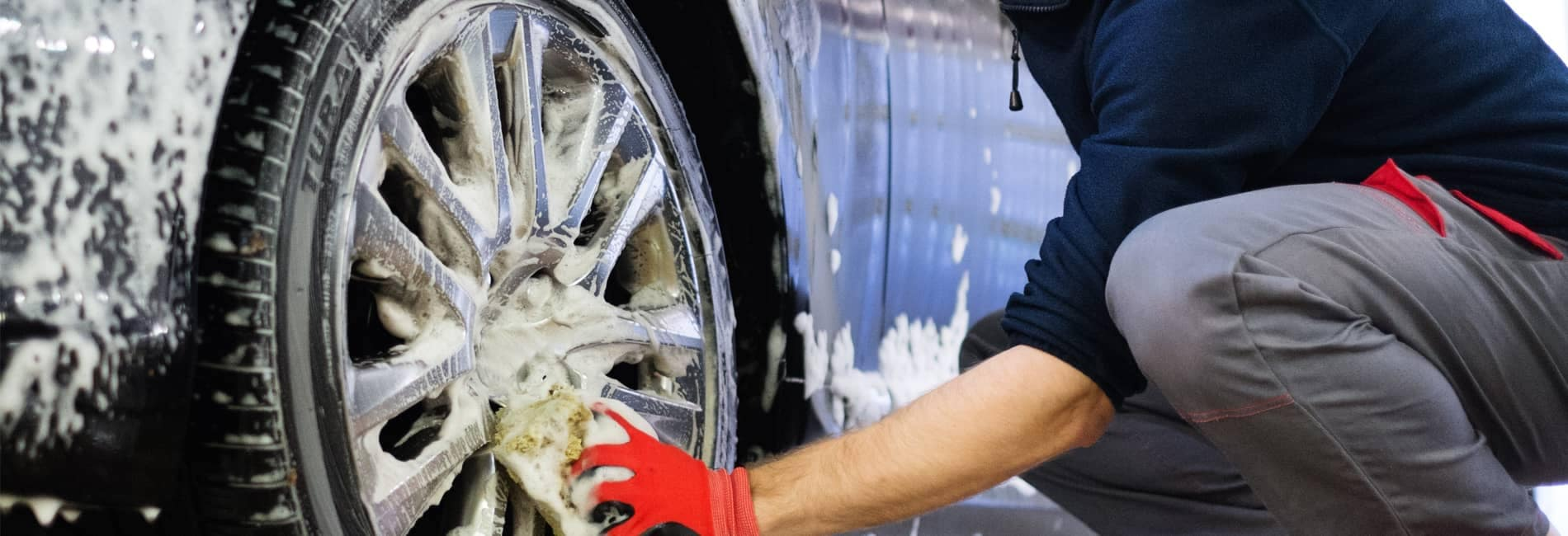 person washing a car tire