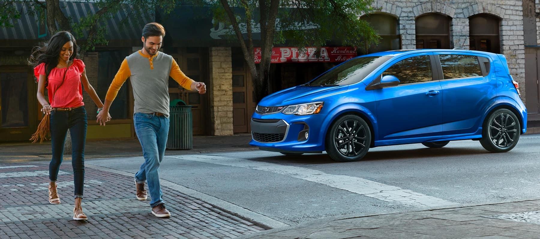 Couple walking across street in front of Chevrolet car