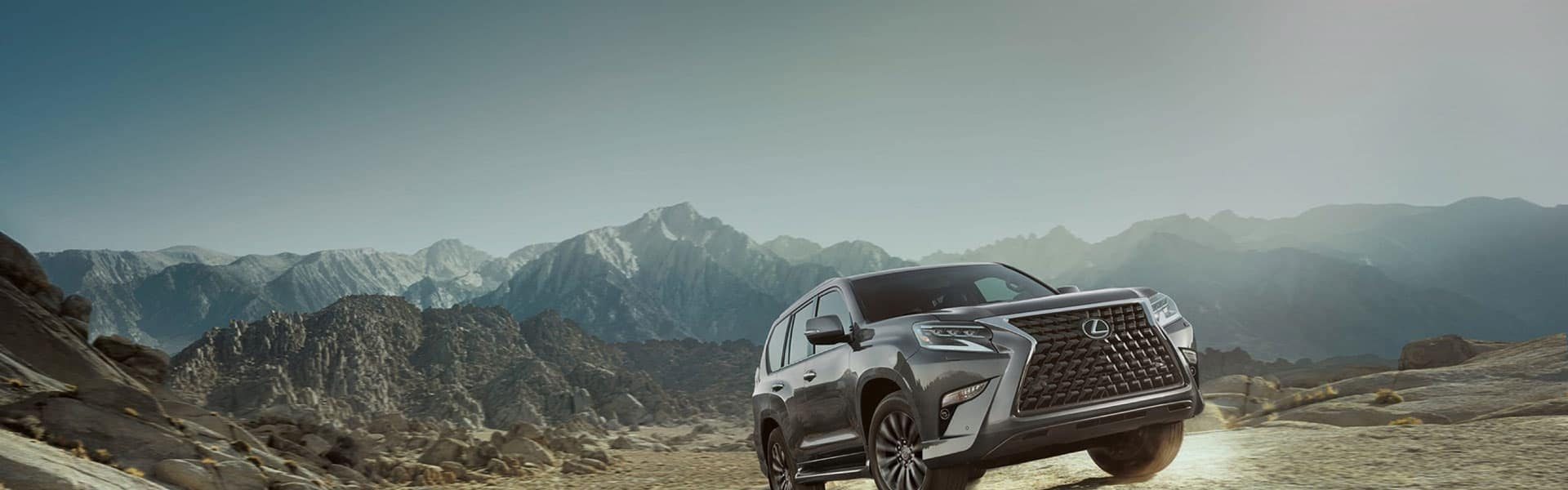Lexus SUV driving up a rocky mountain side with the mountains in the background