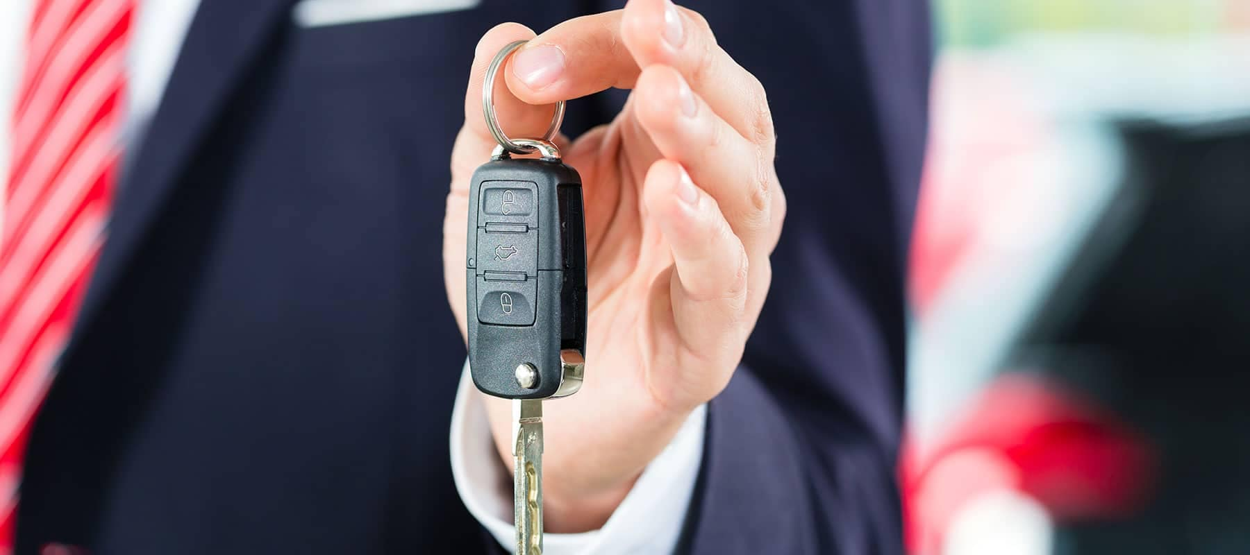 Dealership salesman holding car keys