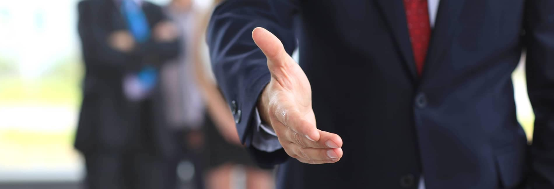 Person in Suit Reaching Out for a Handshake