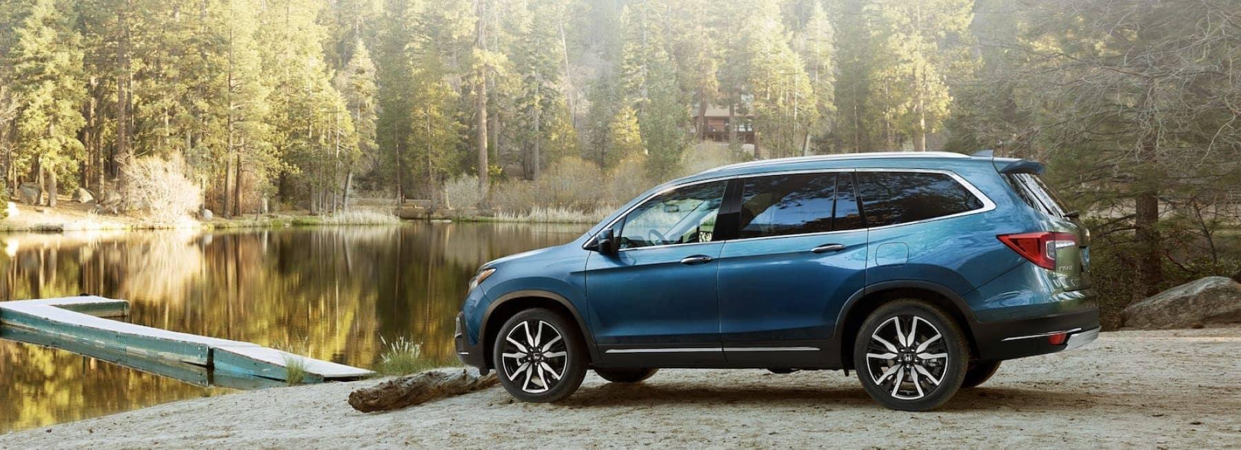 A Honda minivan by a lake.
