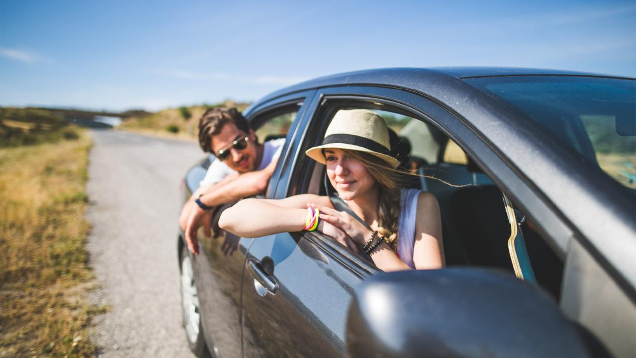 Woman and man hanging out window of car